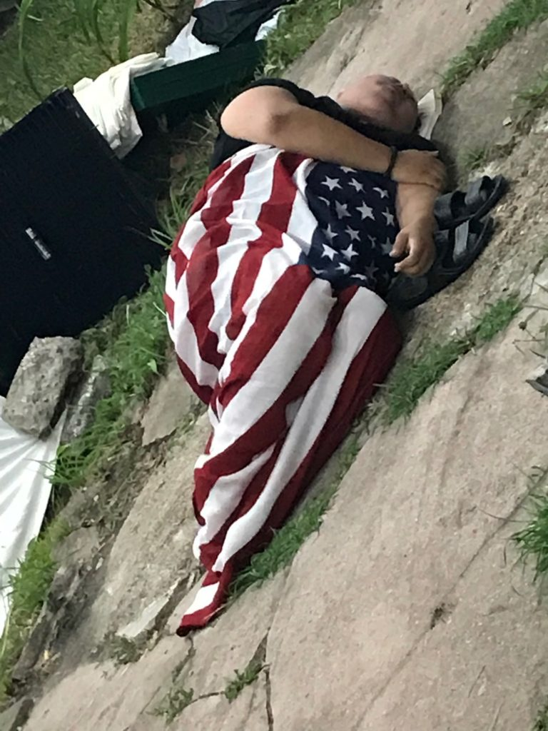 Koomah wrapped in American flag at Failure to Con/Form: Shelter, Casa Anandrea, August 2019. Photo credit: Addie Tsai