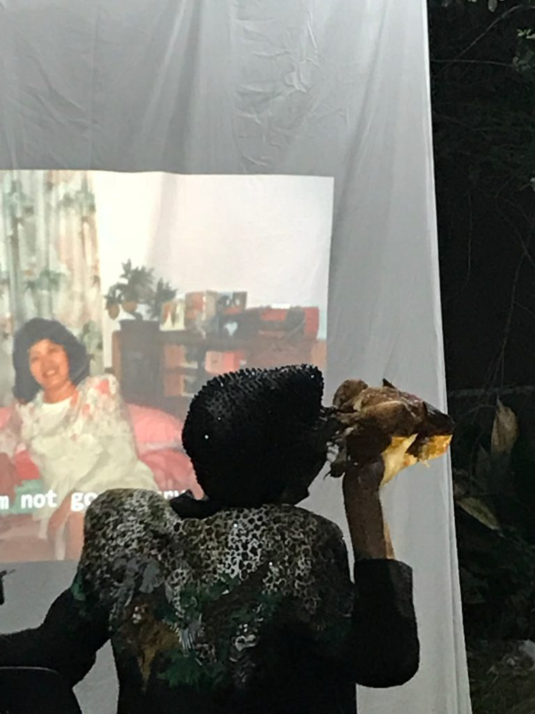 Wo Chan performs with a chicken in front a projection of family at Failure to Con/Form: Shelter, Casa Anandrea, August 2019. Photo credit: Addie Tsai